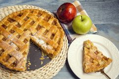 Slice of apple pie on plate next to whole pie. And some apples royalty free stock photography