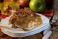 Slice of apple pie on table. Slice of deicious apple pie propped with apples, leaves, decorative forks and plaid, fall colored cloth stock photography
