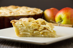 Slice of apple pie, tight and horizontal. Slice of freshly made apple pie, with pastry lattice top, on flat plate with apples, cinnamon sticks and the rest of stock photo
