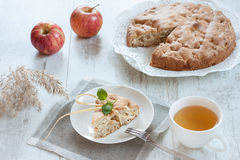 Breakfast with apple pie. Slice of apple pie on the white plate. White wooden table. Apples on the background stock photo
