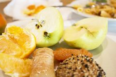 Slice apples, oranges, sweets in syrup. Sliced apples, oranges, sweets in syrup, and sunflower seeds and sweet chips on a white plate royalty free stock image