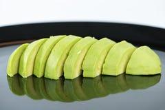 Slice avocado fruit on black dish.  Stock Images