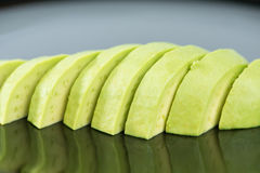 Slice avocado fruit on black dish Stock Photography