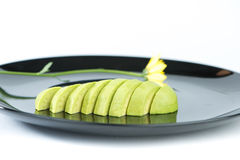 Slice avocado fruit on black dish Stock Images
