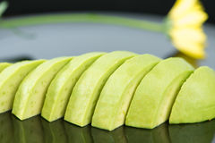 Slice avocado fruit on black dish Stock Image