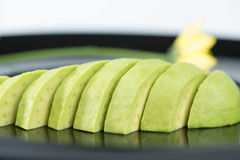 Slice avocado fruit on black dish Stock Photo