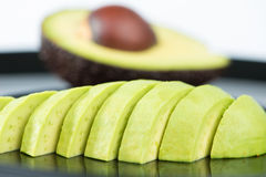 Slice avocado fruit on black dish Royalty Free Stock Images