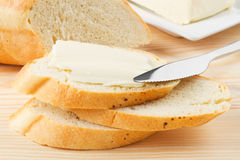 Slice of baguette with butter on wooden board Royalty Free Stock Images