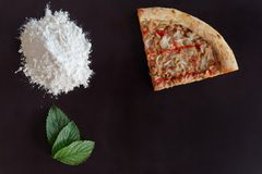 Slice of baked tuna pizza, pile of flour and green leaves on black background. With copy space stock photography