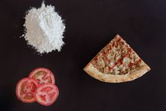Slice of baked tuna pizza, pile of flour and slices of tomato on black background. Directly above photo royalty free stock images