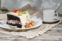 Slice of bird-cherry flour cake with cherries, strawberries and cup of coffee Royalty Free Stock Photo
