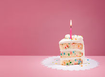 Slice of Birthday Cake with Candle on Pink Stock Images