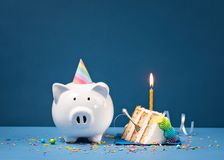 Slice of Birthday Cake with Piggy Bank stock photography