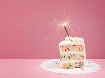 Slice of Birthday Cake with Sparkler. Slice of Colorful Birthday Confetti Cake with a lit sparkler over a pink background Stock Photography