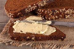 Slice of black bread with sesame seeds and butter on an old wooden background Royalty Free Stock Images