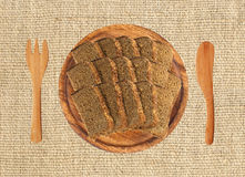 Slice of black rye bread on wooden plate, fork and knife Royalty Free Stock Images
