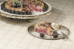 Slice of Blackberry Clafoutis on metal plate with fresh berries Stock Images