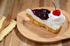 Slice of blueberry cheese cake on wooden plate Stock Image