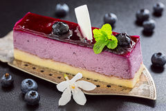 Slice of blueberry mouse cake on old antique cake slicer Royalty Free Stock Photos