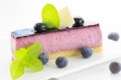 Slice of blueberry mousse cake with mint garnish, on white backg Stock Images