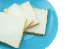 Slice of bread on blue plate with white background Stock Photo