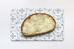 Slice of bread with butter. On bread board isolated on white Royalty Free Stock Photos