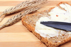 Slice of bread with butter and ears of wheat Stock Photography