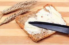 Slice of bread with butter and ears of wheat Royalty Free Stock Images