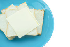 Slice of bread with cheese on blue plate with white background Royalty Free Stock Image