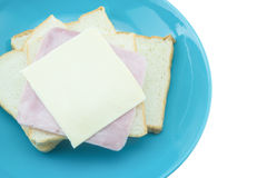 Slice of bread with cheese and ham on blue plate with white back Stock Images