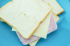 Slice of bread with cheese and ham on blue plate with white back Royalty Free Stock Image