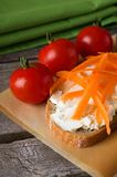 Slice of bread with fresh cheese and carrot shavings Royalty Free Stock Photos