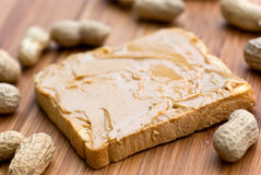 Slice of bread with peanut butter spread on wooden Stock Photos