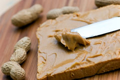 Slice of bread with peanut butter spread on wooden Royalty Free Stock Images