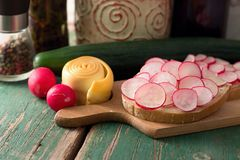 Slice of bread with radish and smoked cheese. Picture of bread slice with butter and cut radishes. Steamed rolled chease and cucumber is placed near wooden board Stock Photo
