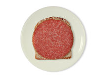 Slice of bread with salami. A slice of bread with salami on a white plate Stock Photos