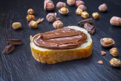 Hazelnut nougat chocolate cream on slice of bread. Slice of bread with spread chocolate cream and hazelnuts on black table. Serving a delicious breakfast concept royalty free stock images