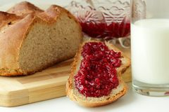 A slice of bread, spread with raspberry jam and a glass of milk Stock Photo