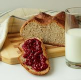 A slice of bread, spread with raspberry jam and a glass of milk Stock Image