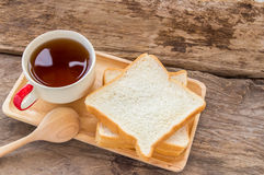 Slice of bread and tea in wooden plate Royalty Free Stock Image