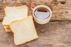 Slice of bread and tea in wooden plate Stock Photo