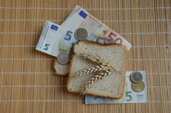 Slice of bread and wheat ears on Euro banknotes Royalty Free Stock Photography