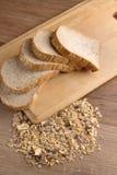 Slice bread and wheat grain on cutting board2.jpg Stock Photo