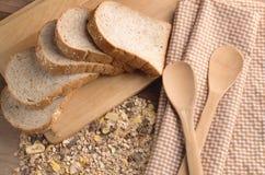 Slice bread and wheat grain on cutting board.jpg Stock Photos