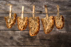 Slice of bread. Slice of whole wheat bread sourdough baked in a wood oven hanging Royalty Free Stock Image