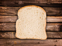 Slice of bread, on wood planks Stock Image