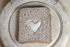 Slice of Brown Bread with White Heart on Vintage Bread Board Stock Photos