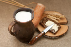 A slice of buttered bread on a wooden board, a crock of milk and mature ears. A summer composition with a slice of buttered bread on a wooden board, a crock of Stock Photos