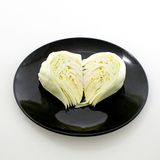 Slice cabbage on black plate isolated on white background Royalty Free Stock Photo