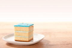 Slice of cake. Rectangular slice of cake with turquoise topping on plate Stock Photos